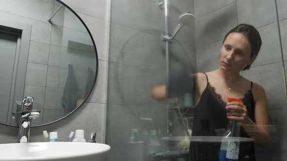 Housewife washing glass doors of shower stall in bathroom with rag.
