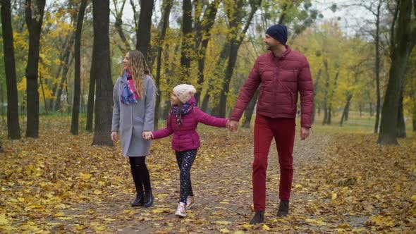 Thumbnail for Cheerful Family with Girl Walking in Autumn Park