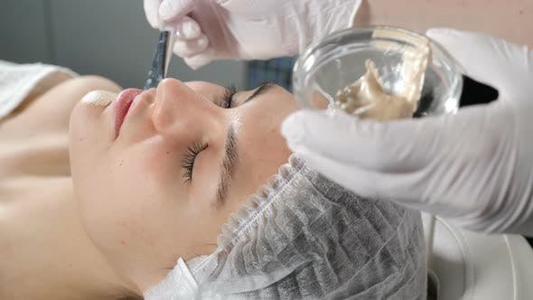 Cosmetician Applying Beauty Mask on Beautiful Female Girls Face. Cosmetic Golden Mask on Face