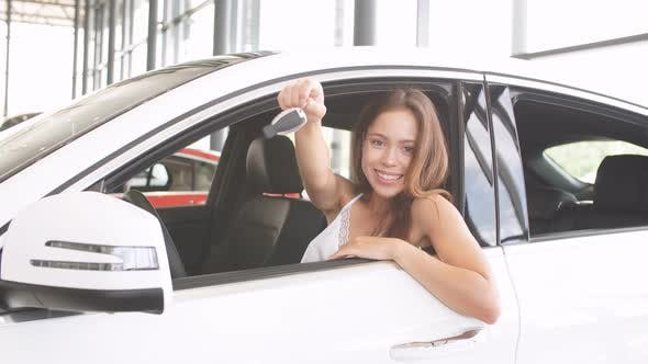 Thumbnail for Happy Woman Driver in White Car Holds Car Keys in Her New Car at Car Show Room