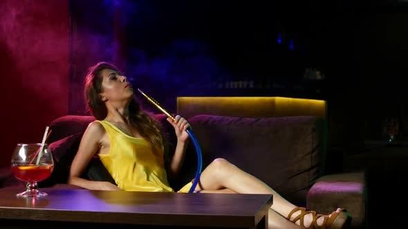 Girl Smoking Shisha Lying on Sofa in Cafe