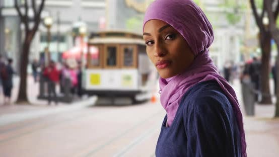 Thumbnail for Black female in hijab texting on phone then turning to smile at camera