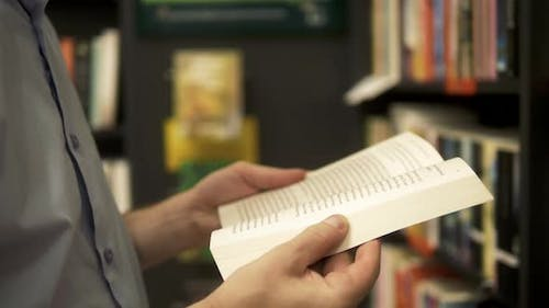 Close-up of Young Caucasian Man in a Bookstore with an Opened Book in His Hands Reading Something