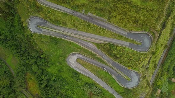 Cover Image for Aerial Top Down Cars Driving on Zig-Zag Winding Serpentine Road, Camera Over Twisted Mountain Road