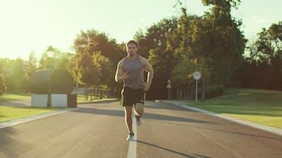Fitness Man Jogging in Park at Summer Morning. Sport Man Training Run