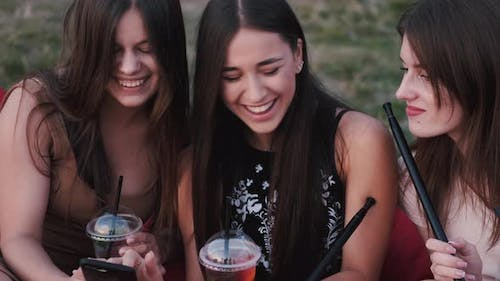 European Girls Are Surfing the Internet on a Smartphone and Having Fun