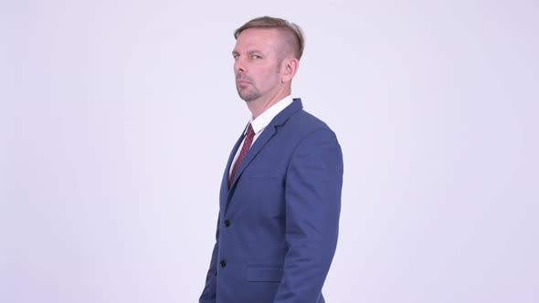 Cover Image for Profile View of Blonde Businessman Looking at Camera with Arms Crossed