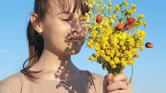 Teen with wildflowers in hands.