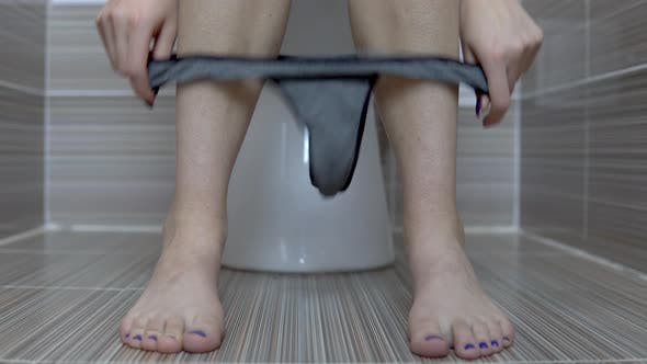 Thumbnail for Woman Shot Gray Tanga Panties Sitting on the Toilet. Girl with Shaved Legs on the Toilet