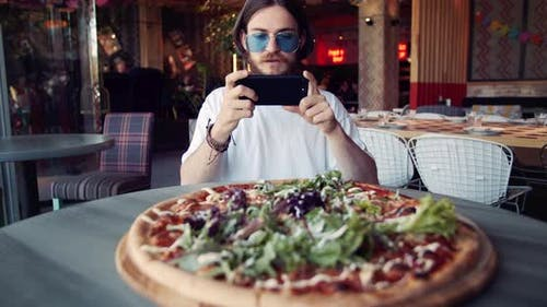 Male Hippie Taking Photo of Pizza