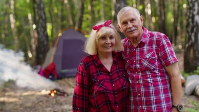 Portrait of Old Happy Couple Resting at Camping in Forest Over Campfire and Tent Background