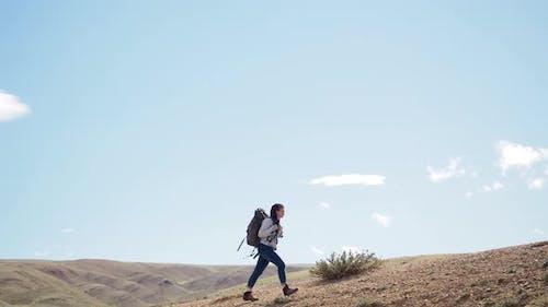 Happy Woman Hiker Trekking on Desert Trail Alone