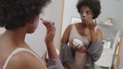 African American Woman Applying Face Mask