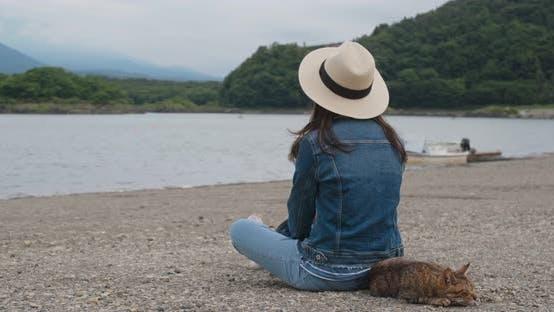 Femme assis au bord du lac avec un chat sauvage dans shojiko du Japon