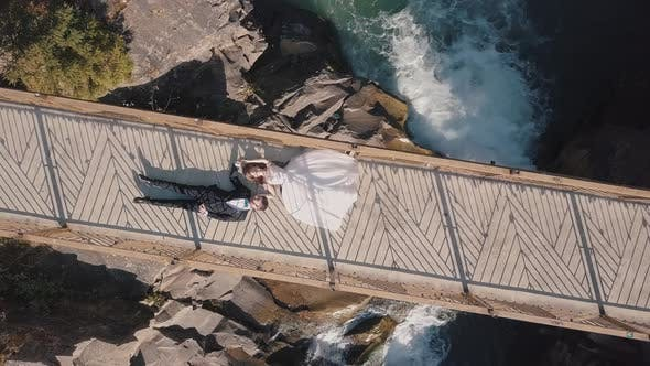 Thumbnail for Newlyweds. Bride and Groom Lie on a Bridge Over a Mountain River. Aerial View