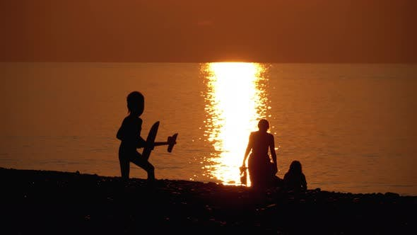 Thumbnail for Silhouette of a Happy Child at Sunset By the Sea Playing with a Toy Airplane. Happy Family.