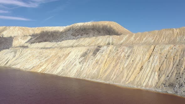 Thumbnail for Hills of pyrite and acid mine drainage water under blue sky 4K drone video