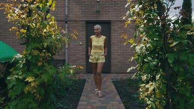 Woman Walking in Her Green Yard