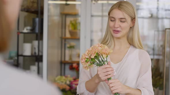 Thumbnail for Happy Female Customer Smelling Carnations and Talking to Florist in Shop