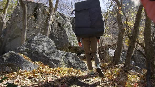 Thumbnail for Young man and woman walking through forest with bouldering gear