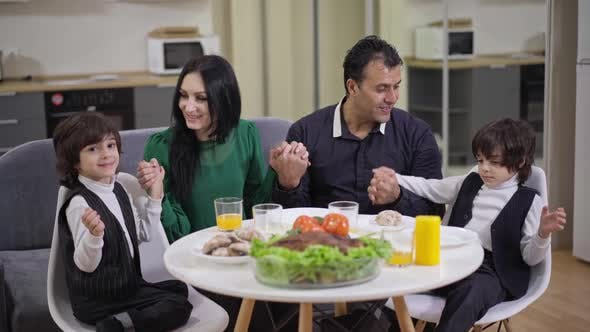 Happy Family Holding Hands Sitting Around Thanksgiving Dinner Table in Living Room at Home