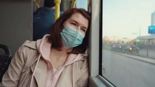 Tired Woman Leaning on Window in Bus