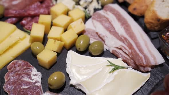 Thumbnail for Closeup of Cutting Board with Sliced Salami, Crackers, Green Olives, Nuts and Berries and Assorted