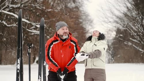 Skiers Spouses Throw Snow in the Winter Forest