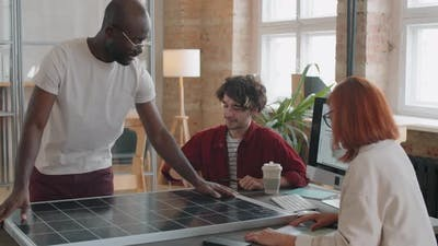 Team of Multiethnic Engineers Discussing Solar Panel in Office