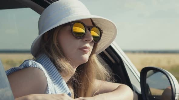 Thumbnail for Happy Young Woman with Sunglasses and Hat Sitting in Car Passenger Seat and Looking Out Window on