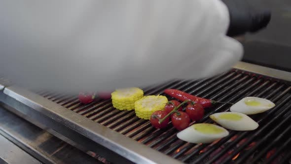 Cover Image for Hands of Chef Putting Vegetable on the Grill in the Restaurant Kitchen