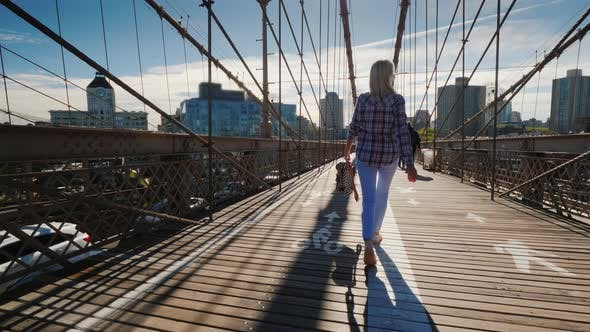 Cover Image for Carefree Woman with a Backpack in Hand Goes on the Brooklyn Bridge in the Early Morning