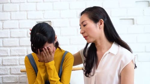 Asian Mother Comforting Crying Teenage Daughter in Miserable Stressed Depressed Sad State of Mind