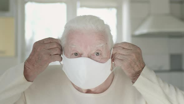 Old Woman Puts On Mask For Protection During Epidemic Of Viral Infection.