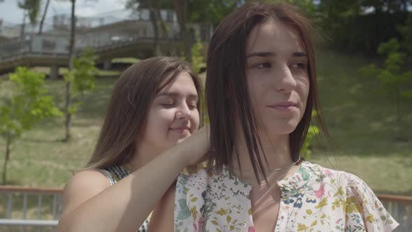 Thumbnail for The Girl Putting a Silver Chain Around Her Friend's Neck