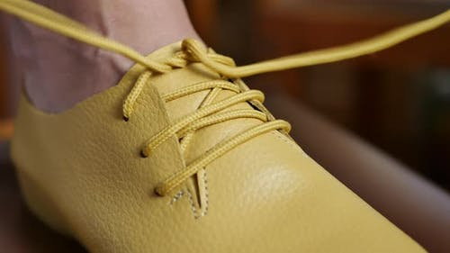 Person Laces Up the Yellow Shoelaces