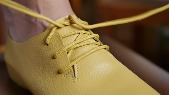 Thumbnail for Person Laces Up the Yellow Shoelaces
