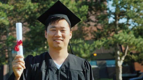 Thumbnail for Portrait of an Asian Man in Graduate Clothes. College Graduation Concept