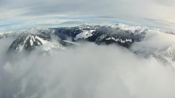 Thumbnail for Sky View Flying Over Snowy Mountain Ridge And Peaks In Rolling Fog Clouds