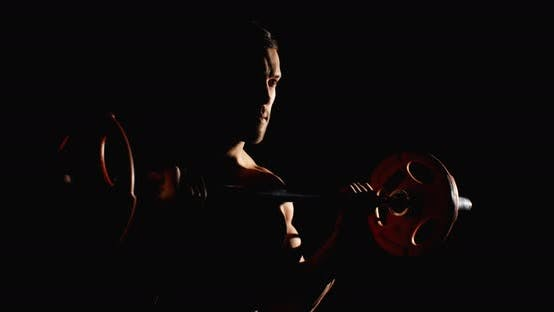 Cover Image for Athletic Man Doing Training In Gym Lifting A Barbell Black Background