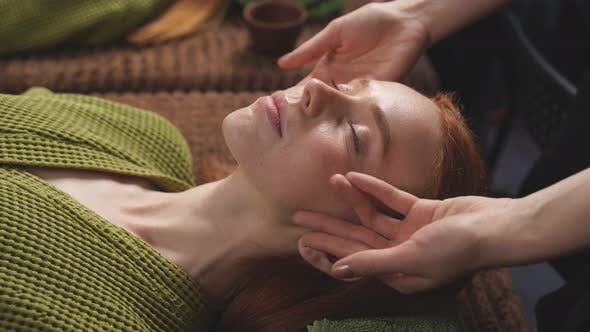 Young Caucasian Woman Receives a Facial Massage with Aromatic Essential Oil for Skin Care From a