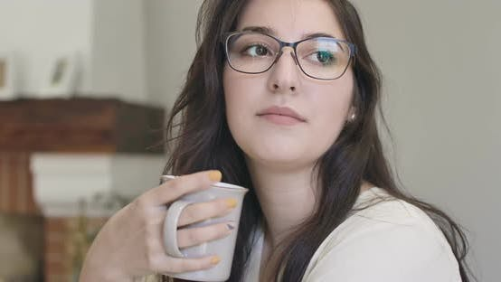 Cover Image for Close-up Face of a Young Thoughtful Caucasian Girl in Elegant Eyeglasses Sitting with a Cup of Tea