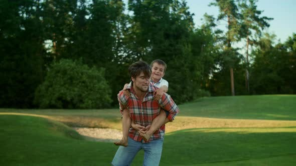 Thumbnail for Father and Son Playing Together in Park. Man Running on Green Field with Boy