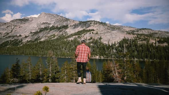 Back View Man Walks Up To Sit By a Woman and Kiss Near Amazing Mountain Lake Scenery