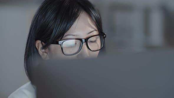 Thumbnail for Schöne Frau, die am Computer am Abend arbeitet