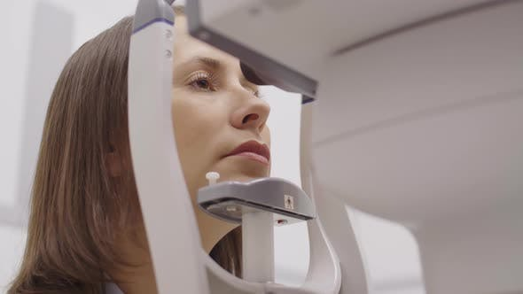 Woman Having Slit Lamp Eye Exam in Optometry Office