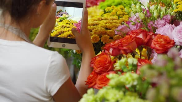 Thumbnail for Florist photographing flowers on tablet