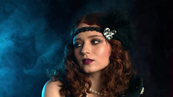 Old-fashioned Sexy Woman Dressed in Style of Flappers Posing on Dark Background with Smoke Neon