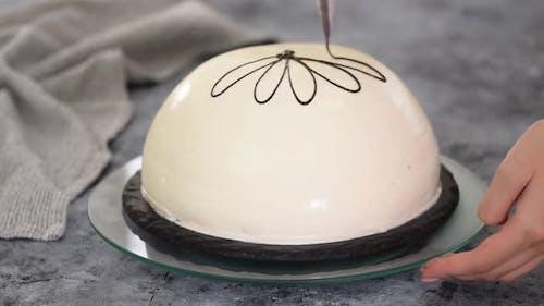 Gießen geschmolzene Schokolade auf einen Kuchen. Pancho Kuchen mit Ananas und saurer Sahne