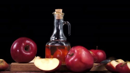 Apple Cider Vinegar Is Rotating on a Wooden Table